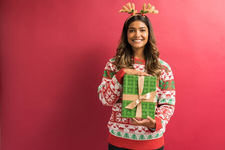 Beautiful young female brunette with Christmas gift isolated against red background