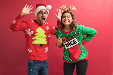 Playful attractive man and woman enjoying Xmas celebration while making eye contact against plain background