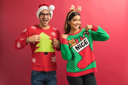 Cheerful Hispanic couple showing their ugly sweaters during Xmas celebration isolated in studio
