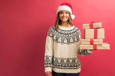 Portrait of smiling pretty woman wearing ugly sweater holding present's stack isolated in studio Stock Photo