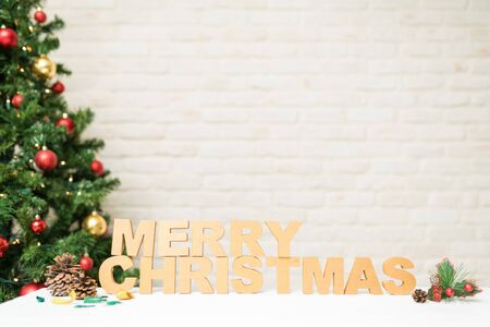 Wooden letters forming Merry Christmas with a lot of copy space and next to a tree with lights