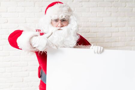 Portrait of male in Santa costume pointing at copy space on blank sign while standing against brick wall