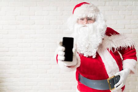 Man in Santa Claus costume showing smartphone screen while making eye contact against white brick wall Фото со стока