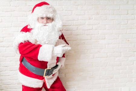 Man in Santa costume gesturing while making eye contact against white brick wall at home
