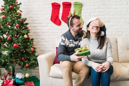 Man surprising woman with present while sitting at home during Christmas