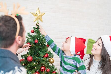 Mid adult parents assisting little boy in putting star on top of tree during Christmas preparations Standard-Bild