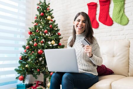 Pretty woman shopping online with credit card on laptop at home during Christmas time