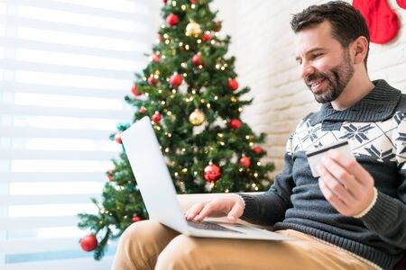 Mid adult man using laptop while shopping through credit card at home in Christmas time