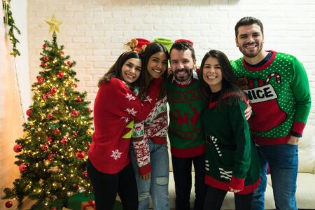 Happy male and female friends wearing ugly sweater while having fun in Christmas celebrations at home