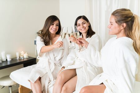 Happy young women toasting champagne flutes while sitting at healthcare center