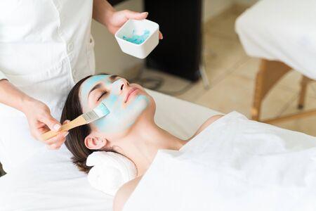 Atractiva clienta hispana acostada mientras esteticista aplicando mascarilla facial con cepillo en el spa de belleza