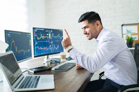 Successful young attractive male finance professional excited about a profitable company while trading stocks in a computer
