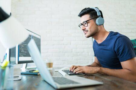 Hübscher junger männlicher Softwareentwickler, der Codes programmiert, während er von zu Hause aus arbeitet