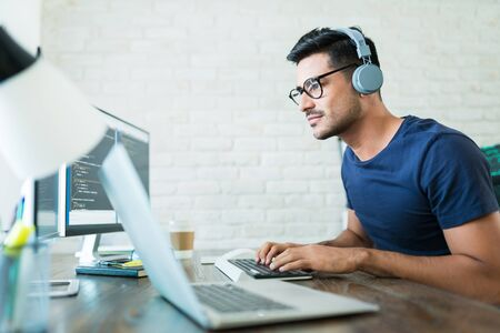 Handsome young male software developer programming codes while working from home