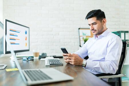 Attractive salesman operating business while using mobile phone at home
