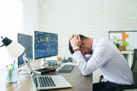 Side view of stressed young broker sitting with head in hands at desk while working from home