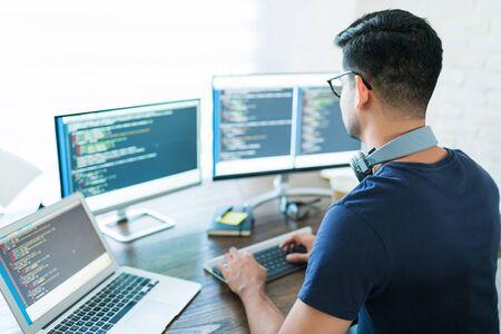 Rückansicht des jungen lateinischen Softwareentwicklers, der während der Arbeit von zu Hause aus programmiert Standard-Bild