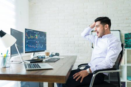 Surprised young Latin freelance trader sitting with mouth open while looking at graphs on computer screens