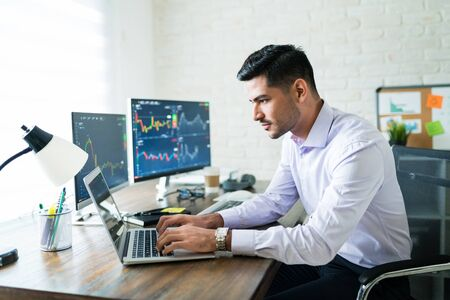 Handsome Latin freelance broker trading through laptop at desk while working from home Banque d'images