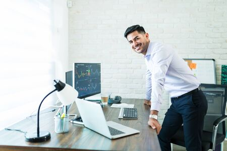 Portrait of young handsome Hispanic finance professional leaning on computer desk while working from home
