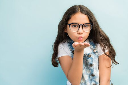 Adorable female child blowing a kiss while making eye contact against plain background Stok Fotoğraf