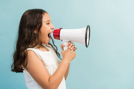 Side view of female child shouting in megaphone while standing against plain background