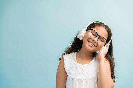 Happy adorable girl listening music through headphones with eyes closed against turquoise background 版權商用圖片