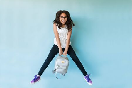 Cheerful preadolescent female student holding backpack in mid-air against turquoise background