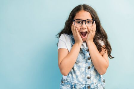 Surprised Hispanic girl standing with hands on cheeks wearing overalls in studio Stockfoto