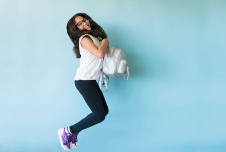 Full length of excited young girl holding backpack while jumping against plain background