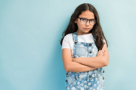 Portrait of upset female child standing with arms crossed against turquoise background Stock fotó