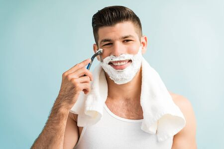 Closeup portrait of smiling good looking male shaving with razor  in studio Reklamní fotografie