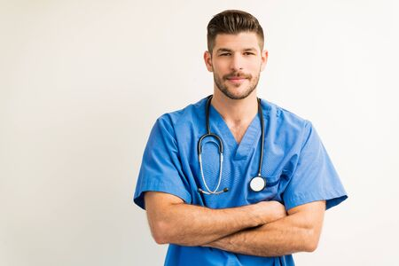 Confident good looking male doctor wearing blue scrubs while standing with arms crossed against white background