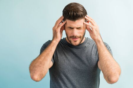 Young male Latin in discomfort suffering from headache while standing against plain background