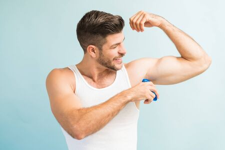 Smiling smart young Latin male applying antiperspirant in armpit while standing against turquoise background