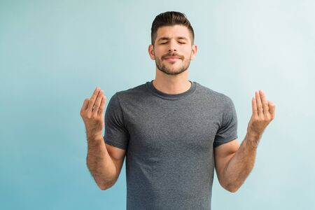 Smart male standing with eyes closed while meditating against turquoise background