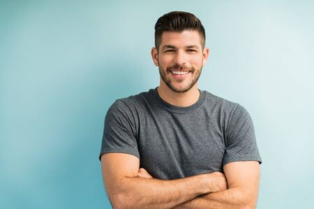 Portrait of handsome smiling Latin man standing with arms crossed against turquoise background