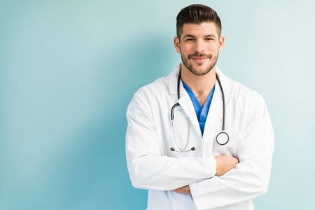 Confident attractive male doctor wearing white lab coat while standing with arms crossed against turquoise background Stock fotó