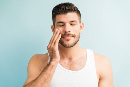 Closeup of rejuvenated man touching his cheek with eyes closed  in studio 版權商用圖片