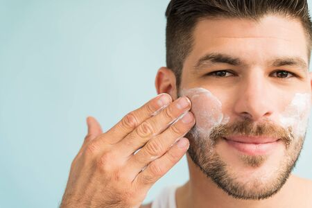 Close-up of attractive male grooming himself with skincare cream on cheeks in studio
