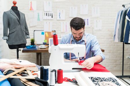 Male clothing designer working on sewing machine at desk in textile industry Imagens - 132052692