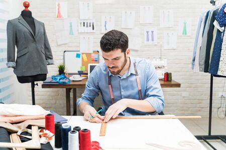 Attractive male Latin dressmaker drawing design on workbench while sitting in factory