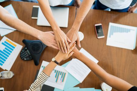 Cropped image of business coworkers stacking hands over desk during meeting at office