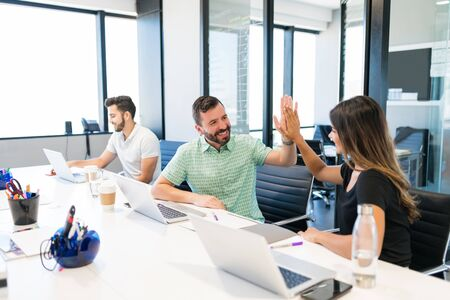 Happy business colleagues giving high five to each other at desk in workplace Stock Photo