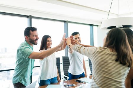 Hispanic business team giving high-fives to each other in beginning of new project at office meeting