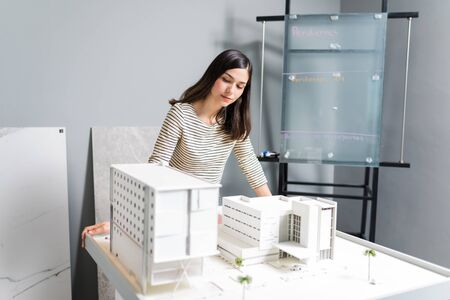 Beautiful young woman architect working on construction project at office