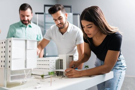 Female professional communicating with coworkers over model in architect workplace Imagens