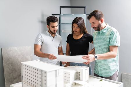 Architectural team planning over blueprint of new model in meeting at workplace