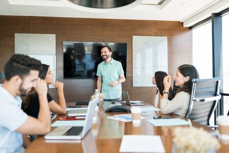 Mid adult boss giving presentation to colleagues in meeting at office Stock Photo