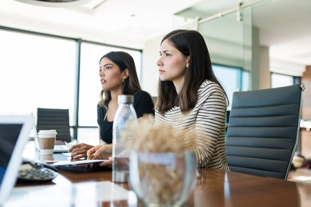 Confident female coworkers looking away while sitting at desk in meeting room Stock Photo